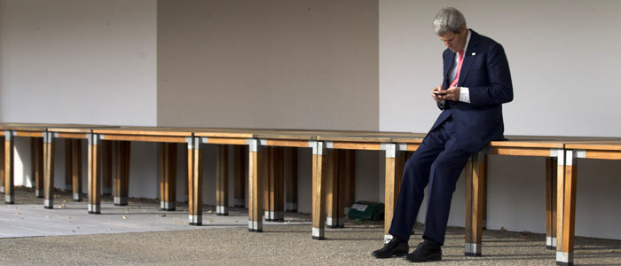 U.S. Secretary of State John Kerry checks his smartphone before a meeting on the Iran nuclear issue in Geneva November 9, 2013. (Reuters)