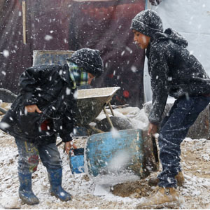 Syrian refugee children carry a cooking gas canister outside their tent during a winter storm in Zahle town, in Lebanon's Bekaa valley December 11, 2013. (Reuters)