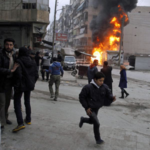 Smoke rises while residents run after what activists said was shelling from forces loyal to President Bashar al-Assad on a fuel vendor in Aleppo, December 10, 2013. (Reuters)