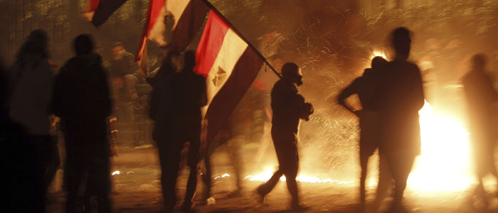 A protester is seen carrying national flags while walking near flames from Molotov cocktails thrown during clashes with riot police near Cairo's Tahrir Square (Reuters file).