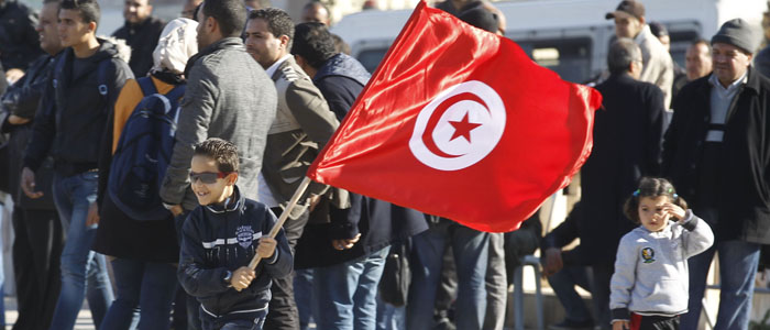 A boy waves a Tunisian flag as he runs during a rally in Tunis marking the third anniversary of the country's revolution Dec. 17, 2013. (Reuters)