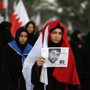 "An anti-government protester holds a leaflet drawing attention to the case of an imprisoned photographer, in Budaiya, west of Bahrain's capital, Manama, December 13, 2013. The leaflet reads in part: ""Silence Kills Democracy.""  (Reuters)"