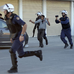 Bahraini riot police arrest an anti-government protester during clashes in Sanabis, west of Manama, December 3, 2013. (Reuters)
