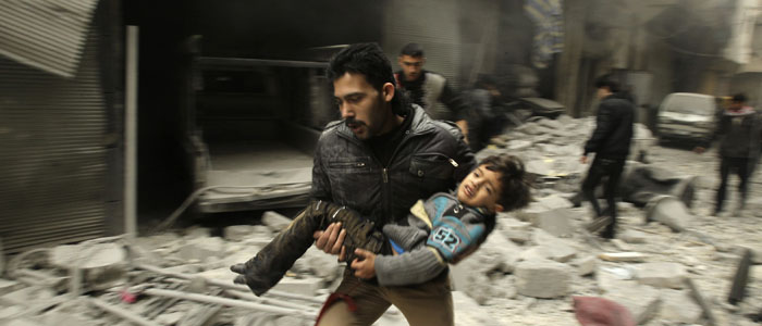 A man runs as he carries a child who survived what activists say was an airstrike by Syrian government forces in Aleppo Jan. 21, 2014. (Reuters)